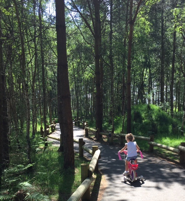 little girls cycling through Center Parcs Woburn Forest - top tips, take a bike with you