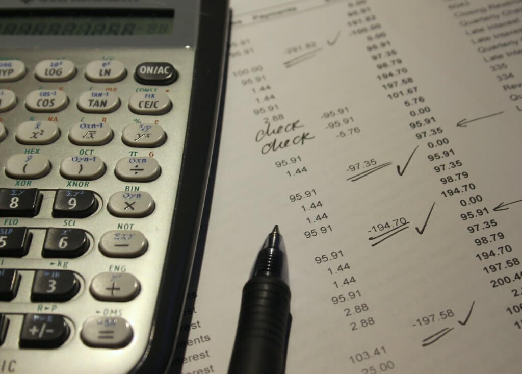 Calculator and bank statements being ticked for mortgage application