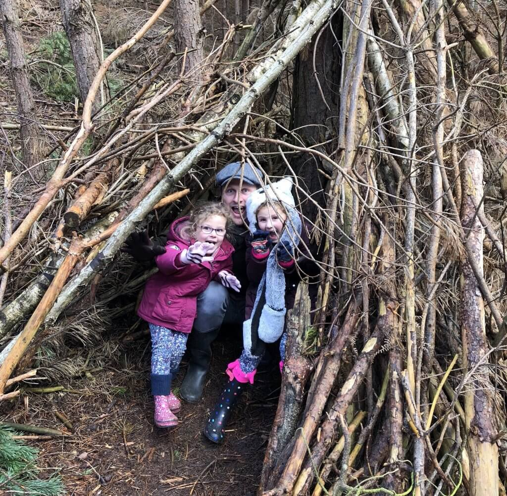 My girls and daddy in woodland den - free half-term activities