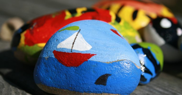 Colorful rock painted with a sailing boat