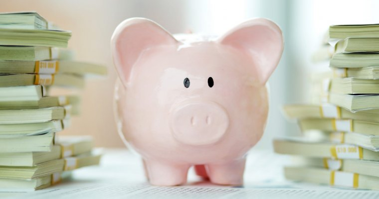 Image of pink piggy bank surrounded by stacks of dollar bills - guide to saving for your children