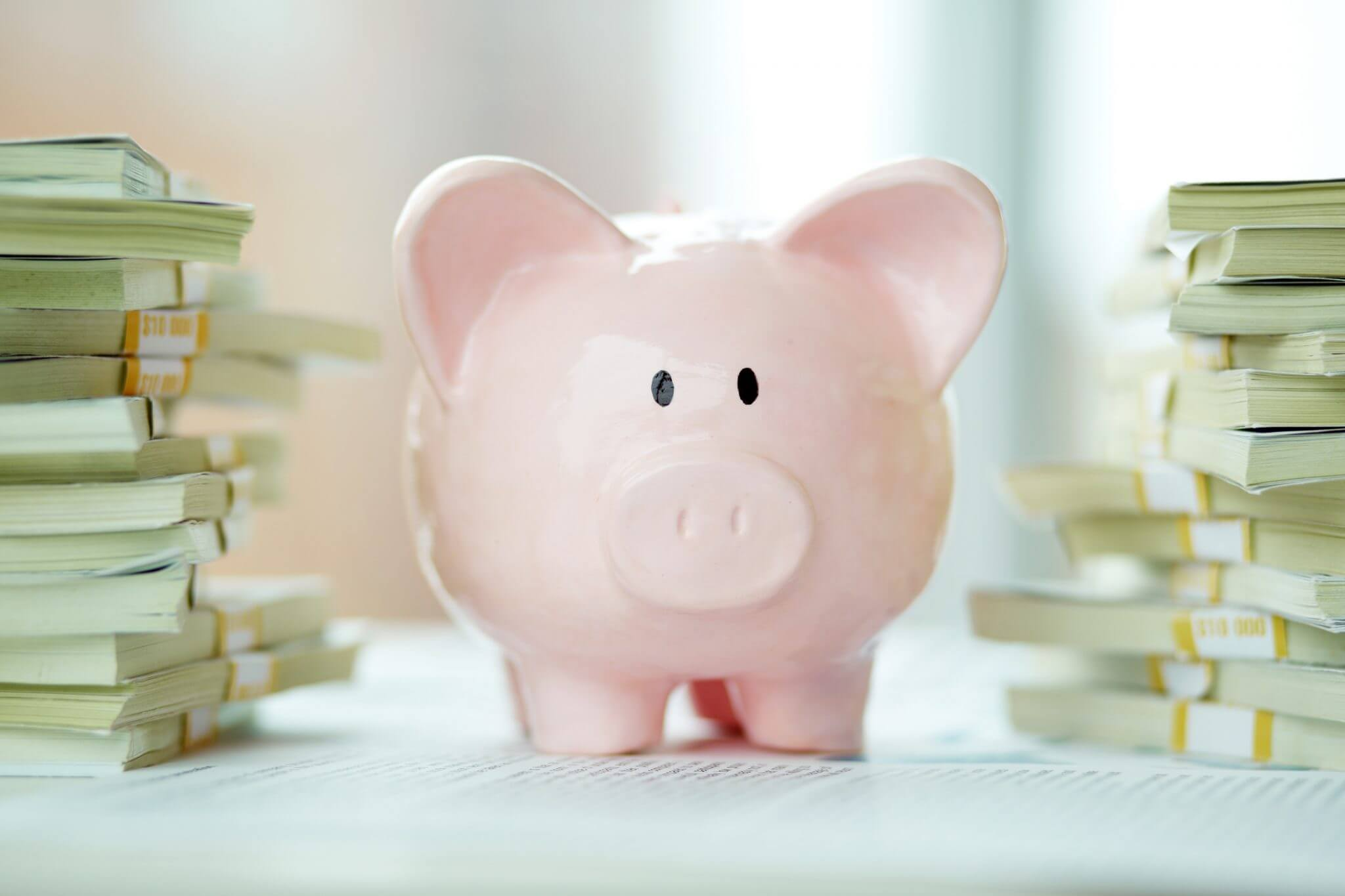 Image of pink piggy bank surrounded by stacks of dollar bill