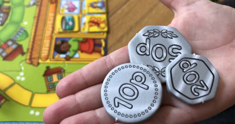 Child holding pretend money from Pop to the shops game - great games to teach children about money