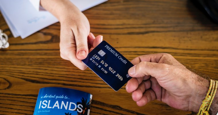 Handing over credit card to book a holiday - travel tips to save money